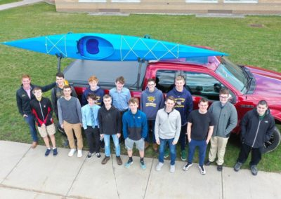 students with kayak on truck